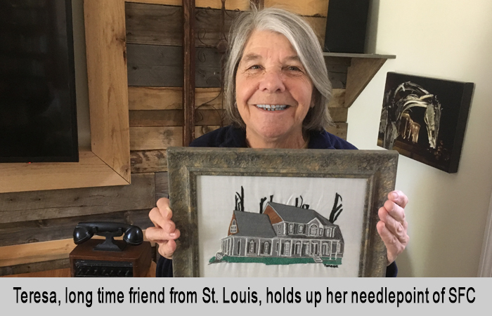 Teresa, long time friend from St. Louis, holds up here needlepoint of St Francis Cottage