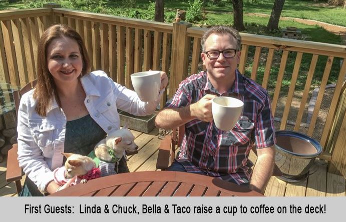 First guests, Linda and Chuck with their dogs Bella and Taco raise a cup of coffee on the deck.